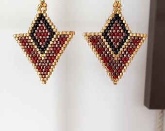 Earrings are made of gold and Burgundy