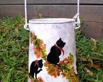 shadows of cats with flowers painted on retro milk bottle