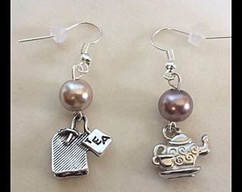"Mismatched earrings show a ""tea and his bag"""