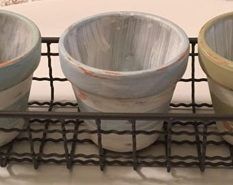 Hand painted terra cotta pots in wire basket