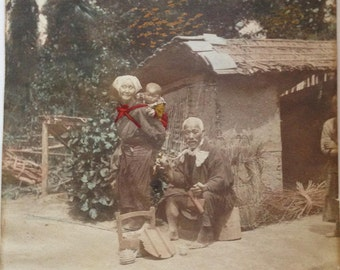 Japanese Meiji Era Albumen Hand Colored Photograph Print Japanese Peasant Couple w Baby Taking Tea in a Garden Setting Kizuru Smoking Pipe