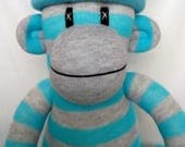 Cheeky grey and turquoise striped Sock Monkey with floral design pom pom hat