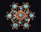 Vintage Starburst Flower Brooch in Gold Tone Metal with Blue Rhinestones