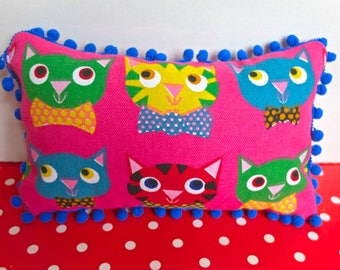 Cushion for child with pom poms sewn into a fabric rose print cats