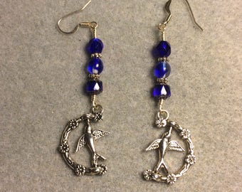 Silver spinning bird charm earrings adorned with cobalt blue Czech glass beads.
