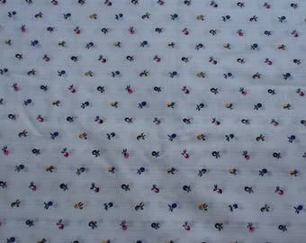 """Lightweight cotton fabric, white with purple, pink, yellow and blue flowers. By the yard, 44"""" wide."""