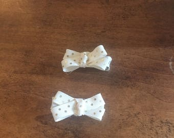 A set of small cream bows with gold polka dots