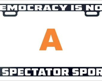 Democracy is not a spectator sport funny assorted license plate frame