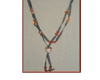 Stick it in black organza and orange crystallized beads + heart pendant