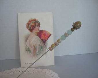 An Antique hatpin holding an Antique beads