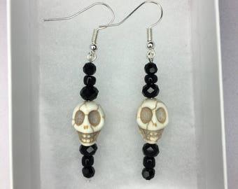 Skull dangle earrings with black glass beading