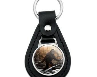 Bigfoot sasquatch walking in the woods black leather keychain