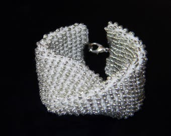 The bracelet is crocheted from white cotton and silvery beads