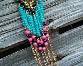 Long, Gold dangly beaded necklace with pink, black and blue beads