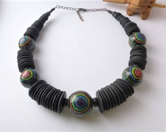 Crew-neck ethnic African necklace hand made designer black lozenges and multicolored rainbow polymer clay beads.
