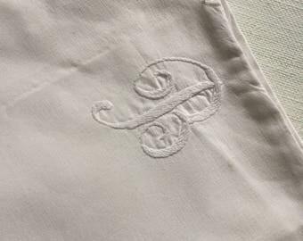 """A crisp white monogrammed """"B"""" vintage bolster cover"""
