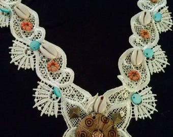 Bib is decorated with beads color white