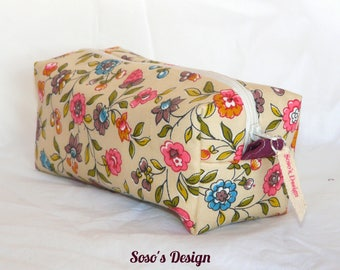 Purse with pink and blue flowers on beige background