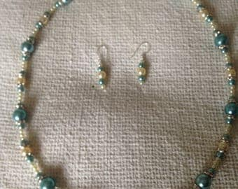 Ladies blue and cream faux pearl necklace and earring set.