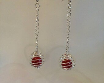 Earrings with cages and red beads