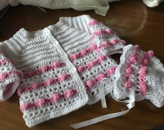 White and pink baby jacket and bonnet.