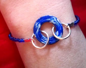 Bracelet with blue seed beads and metal pendant