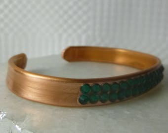 Emerald Empress is a copper cuff bracelet highlighted on the front with emerald flat back crystals