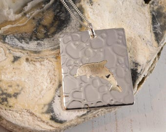 Silver Dolphin Pendant: A dancing dolphin on a textured sterling silver pendant
