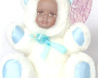 """Foxy, a 5"""" plush blue and white teddy bear with an African American face with a dark blone curl, has real eyelashed"""