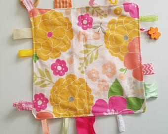 """Teething Chew Tag blanket for baby. Yellow & Pink flowers, ribbon, wood ring pendant, button. Measures 10""""x10"""". Handmade by Everyday Gourmet"""