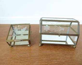 Two brass and glass display boxes with mirrored bottoms and etched flower lids