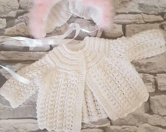 White and pink pram set, baby girl cardigan and hat with fur trim.