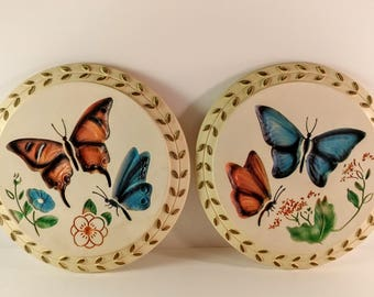 Set of 2 Mid Century, 1960's Modern Art Co. Round Chalkware Wall Plaques. White with Blue & Brown Butterflies, Flowers and Gold Leaf Rim.
