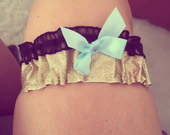 Gold glitter garter with black lace trim and blue ribbon