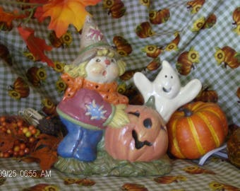 Scarecrow with pumpkin and ghost lighted