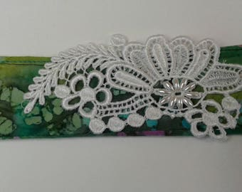 "Fabric bracelet made of green and pink batik. Lace with pearls on front, button closure. 8.5"" x 2"""