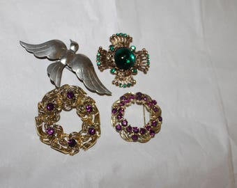 4 Brooches in This Lot, Bird, Two Round, One Cross  Like.  The are jewels of some kind in three of them, green ruby like, Purple, and Green