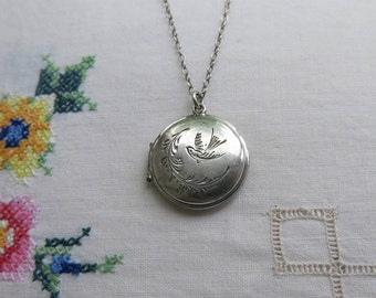 Silver locket engraved with a swallow