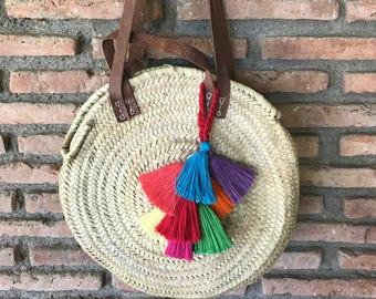 Round straw basket with pom-poms