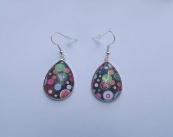 Drop earrings print glass cabochon and silver polka dots and spirals on black background.