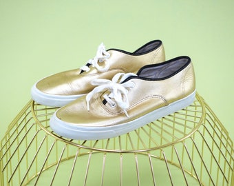 Unique find gold leather nine west tennis shoes with black tongue and trim around upper