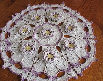 round doily with bicolor flowers on white background and purple gradient crochet