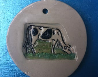 Cow hanging in white stoneware decorative disc