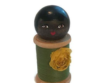 Doll: Vintage Wood Spool with green thread and a yellow flower.