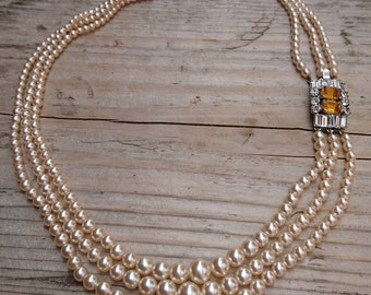 Three strand pearl necklace with a rhinestone clasp