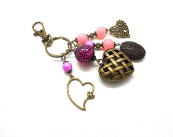A scent! bronze bag charm, heart and beads in shades of pink and purple charms and co.