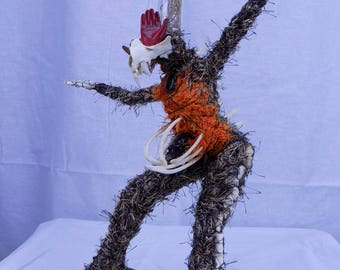 Taxidermy doll/sculpture with preserved roots, beetle, spider, and cat bones
