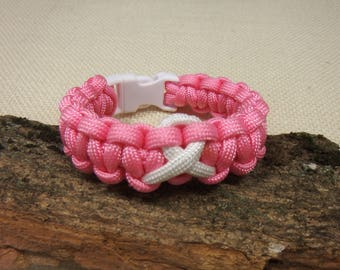Cancer awareness paracord bracelet, pink with centered white awareness symbol, sturdy white snap in  buckle