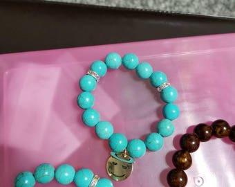 Turquoise elastic band beaded bracelet with Angel emoji charm.