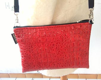 "Pochette plate rouge ""croco"" or electric blue and its shoulder strap."